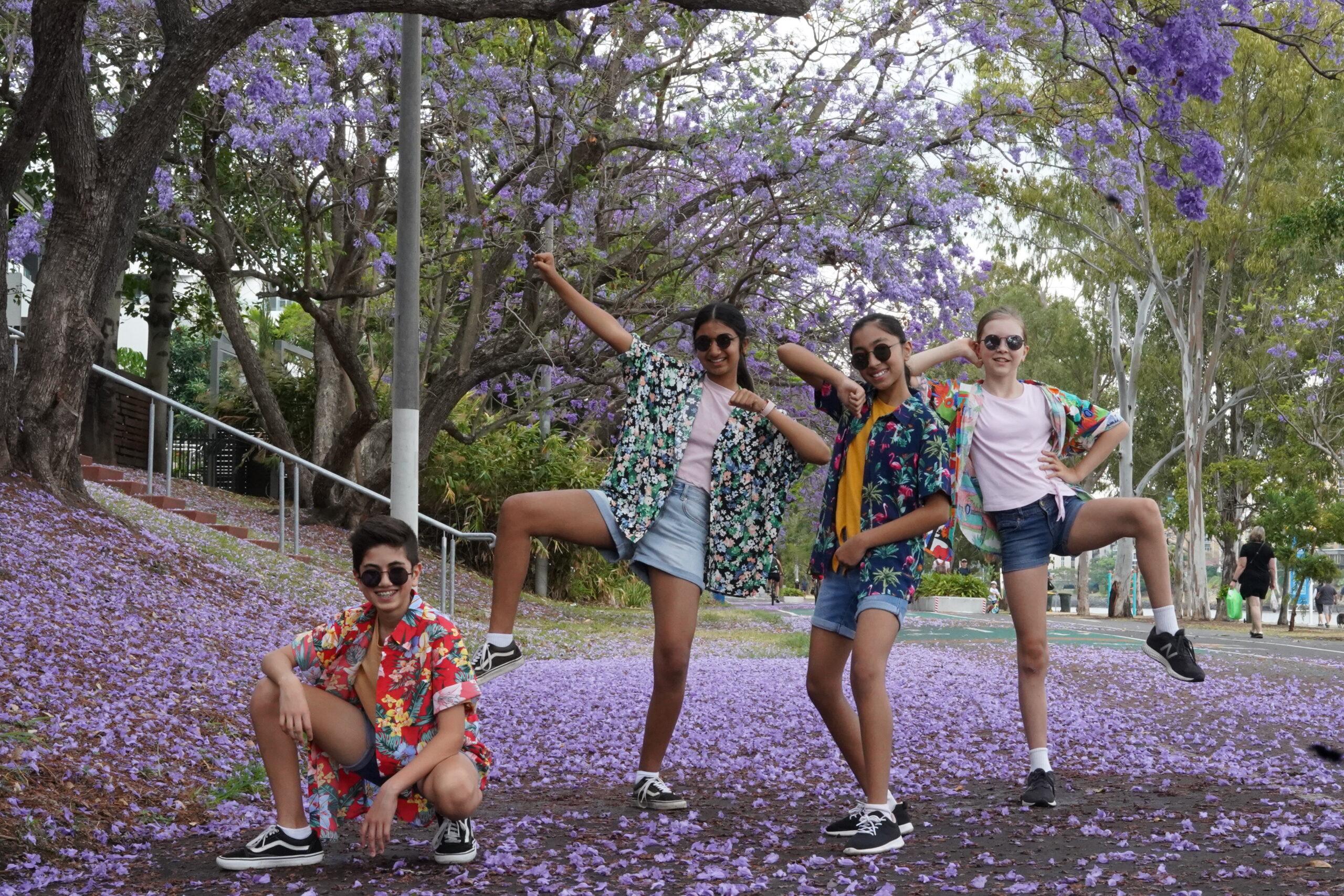 Chingari Crew - Four teenagers posing in dance poses underneath a Jacaranda Tree