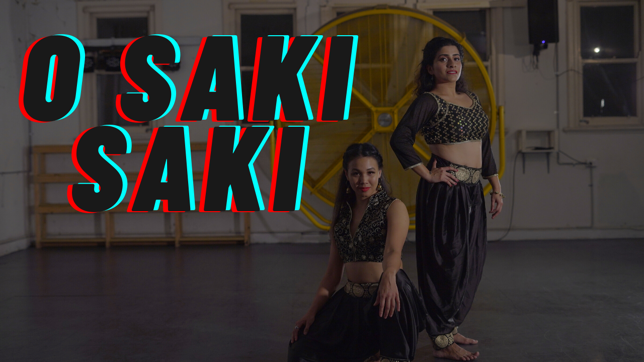 A woman sitting and a woman standing looking at the camera with the words O Saki Saki